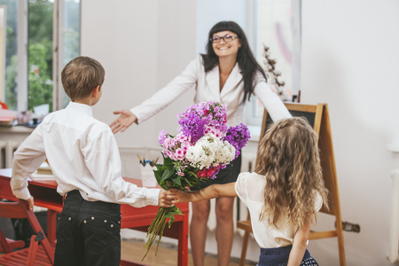 Boy and girl children give flowers as a school teacher in teacher's day Stock Photo