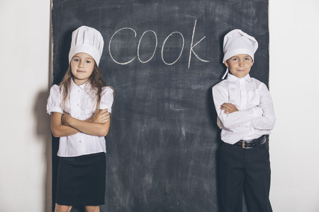 elective: Boy and girl cooks with slate Board under the text menu in the Studio