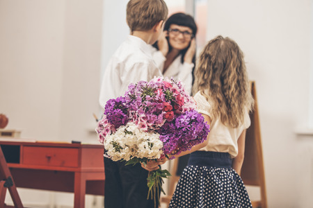 Boy and girl children give flowers as a school teacher in teachers day Reklamní fotografie