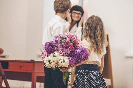 Jongen en meisje kinderen geven bloemen als een school leraar in dag van de leraar Stockfoto