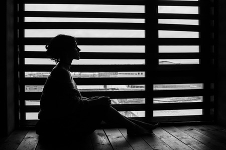Woman silhouette at the window of the house in winter, gentle and pensive sitting on the floor Standard-Bild