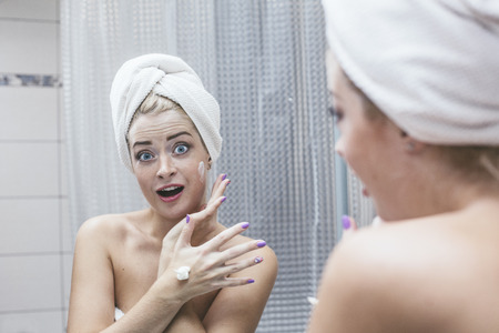 eyelids: Young woman in a bathroom holds a cosmetic procedures to enhance beauty and health in a towel