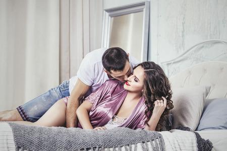 カップル男と女、若くて美しい愛に一緒に、幸せなロマンチックな日に寝室でホームします。