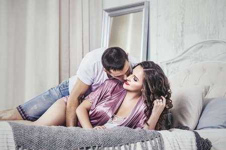 Couple man and woman, young and beautiful home in the bedroom on a romantic date together in love and happy
