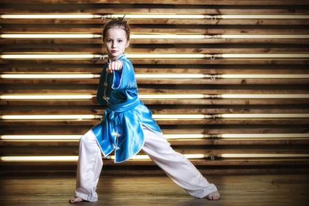 格闘技のためのスポーツウェアの部屋でかわいい女の子は武術やカンフー