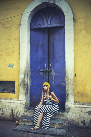 Young beautiful happy woman on a background of blue wooden door of a house with yellow walls