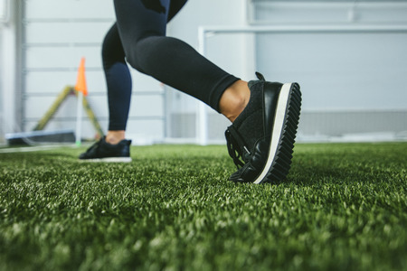 Slender young woman in sportswear is engaged in the sports stadium closeup of feet