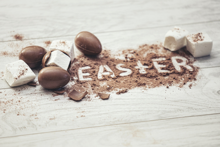 Chocolate Easter eggs with marshmallow and cocoa that says Easter on the table Stock Photo