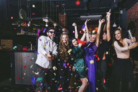 Young cheerful company of friends in the club bar having fun with multi-colored confetti and crackers celebrate the holidays