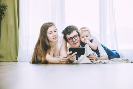 Family mom, dad and baby are doing selfie on phone lying on the floor of the house
