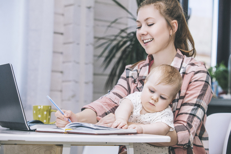Family mother works with a laptop via the Internet and the baby happy together at home smiling Stock Photo