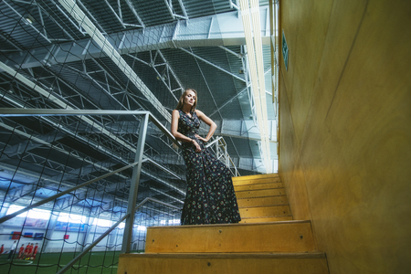 Beautiful young fashion model in a dress at a large sports stadium in the stands posing