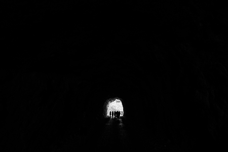 People are in a dark tunnel in the rock silhouettes on a light background input