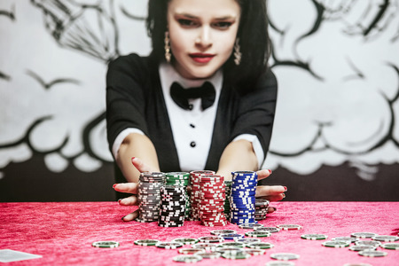 Woman beautiful young successful gambling in a casino at a table with cards, chips and alcohol closeup