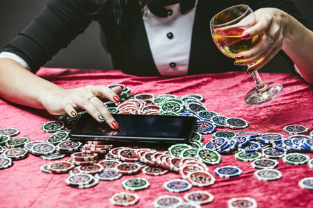 Beautiful young woman with a successful gambling tablet, online casino at a table with cards, chips and alcohol closeup