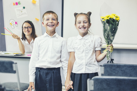 Beautiful children school children with flowers for the teachers at school on a holiday