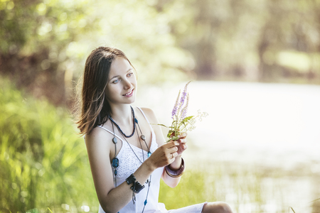 Beautiful and happy young woman in nature in hippie style with a bright Sunny day