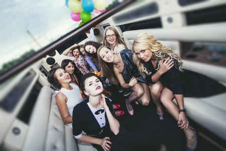 Jonge mooie gelukkige vrouwen vieren vrijgezellenfeest in een converteerbare limousine Stockfoto