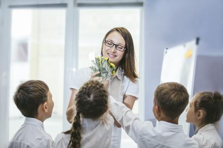Niños de la escuela de los niños hermosos con flores para los profesores en la escuela en un día de fiesta Foto de archivo - 84430054