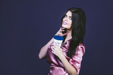 Modell Frau jung und schön in einem Pop-Art-Stil auf einem lila Hintergrund mit einem Bild von einer Tasse Kaffee Standard-Bild - 84430258