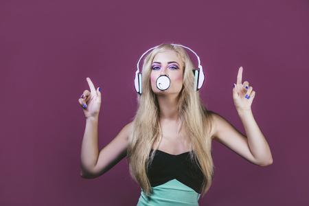 Vorbildliche Frau jung und schön im Stil der Pop-Art auf einem rosa Hintergrund gemalt mit Kopfhörern und Kaugummi Standard-Bild - 84430095