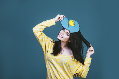 Model woman young and beautiful in the style of pop art on a blue background painted in a cap with a crown