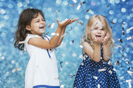 Two little girls child fashion with silver confetti in the background with patches of cute and beautiful Reklamní fotografie - 84589549