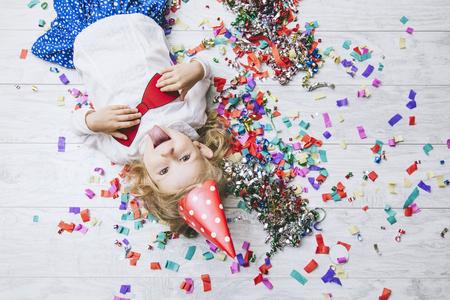귀 엽 고 아름 다운 멀티 색종이 바닥 및 축제 모자에 아름 다운 작은 소녀 자식 행복 한 행복 한 활