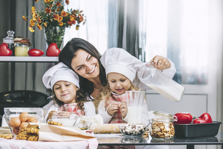 Mother and two happy little baby girl drinking milk and cook at the table in the kitchen is lovely and beautiful Stock Photo