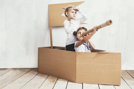 Dwoje dzieci małe dziewczynki w domu kartonowym gra kapitanów i marynarzy