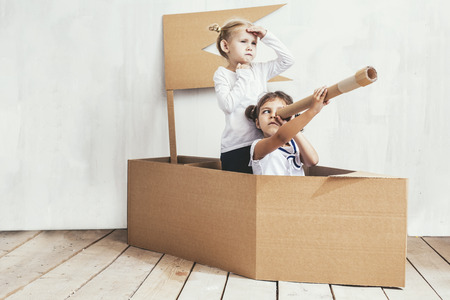 Two children little girls home in a cardboard ship play captains and sailors Stok Fotoğraf