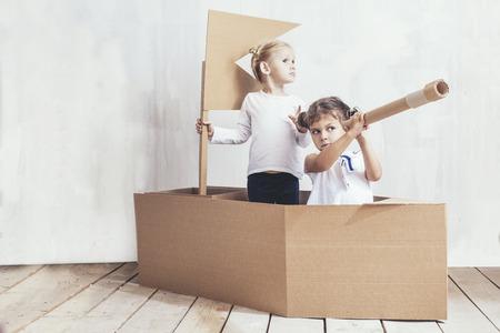 Twee kinderen meisjes thuis in een karton schip spelen kapiteins en zeelieden