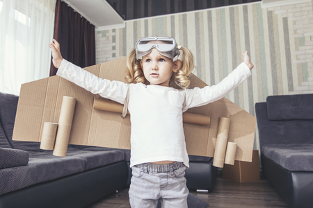family sofa: Child plays in the costume of the pilot and wants to fly in the sky Stock Photo