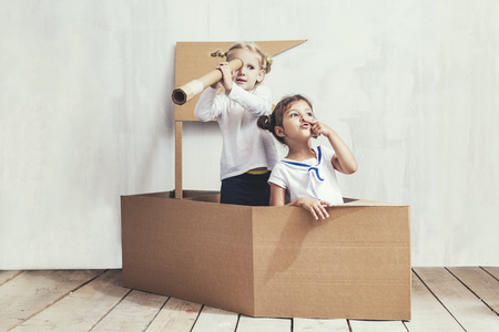 Two children little girls home in a cardboard ship play captains and sailors 写真素材