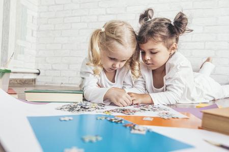 두 아이, 취학 연령의 어린 소녀가 바닥에 퍼즐을 넣어