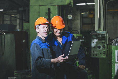 Two workers at a manufacturing plant with a laptop in hand on the background of the equipment