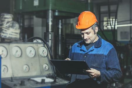 Werken in de plant met tablet in handen op de achtergrond van de apparatuur