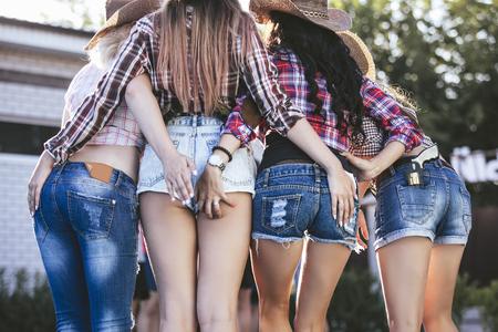 Frauen sind zu Priestern in Jeans Shorts jung schön sinnlich auf der Party zusammen in Cowboy-Stil Standard-Bild - 88679918