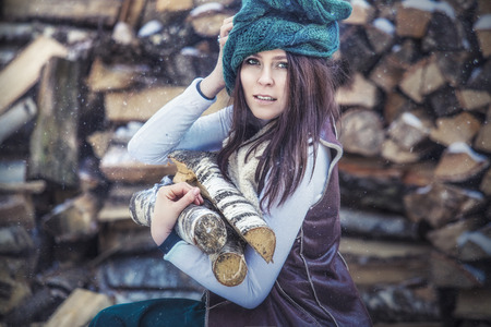 Portrait of a beautiful fashionable young woman with wooden logs for the fireplace in the winter on the background of firewood
