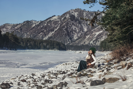 Beautiful fashionable young woman in winter on a background of mountains and rivers on the edge of the forest