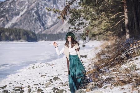 Mooie modieuze jonge vrouw in de winter op een achtergrond van bergen en rivieren op de rand van het bos Stockfoto