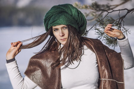 Portrait of a beautiful fashionable young woman in winter with a branch of a tree in a headdress