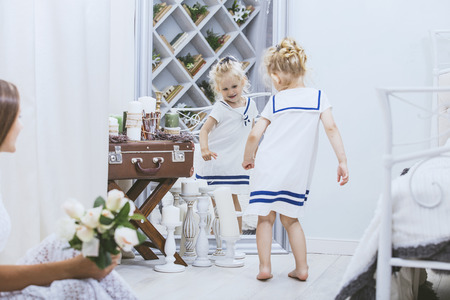 Happy beautiful little girl in a white dress at home of a large mirror in the bedroom Banco de Imagens