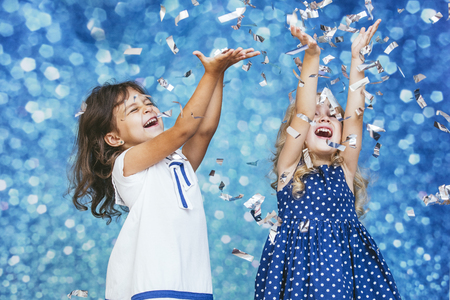 Two little girls child fashion with silver confetti in the background with patches of cute and beautiful