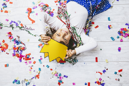 Little girl child cute and beautiful with multi-colored confetti on the floor happy is happy in a paper crown  Princess Stock Photo