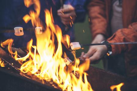 グリルクローズアップで火の上にマシュマロを焼く友人の手