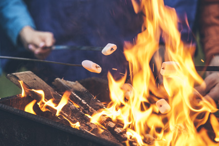 Hands of friends roasting marshmallows over the fire in a grill closeup Фото со стока
