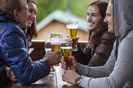 amigos felices sentados con gafas altos de cerveza en la mano sobre una mesa de madera Foto de archivo