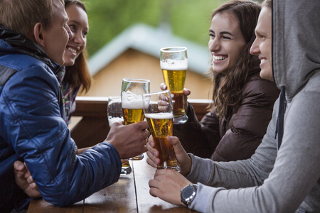 Happy friends sitting with tall glasses of beer in hand at a wooden table