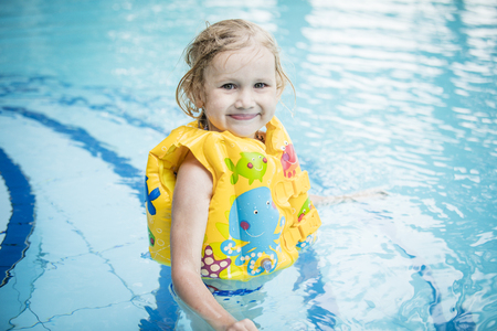 Little happy girl smiling and swimming in the outdoor pool beautiful and happy